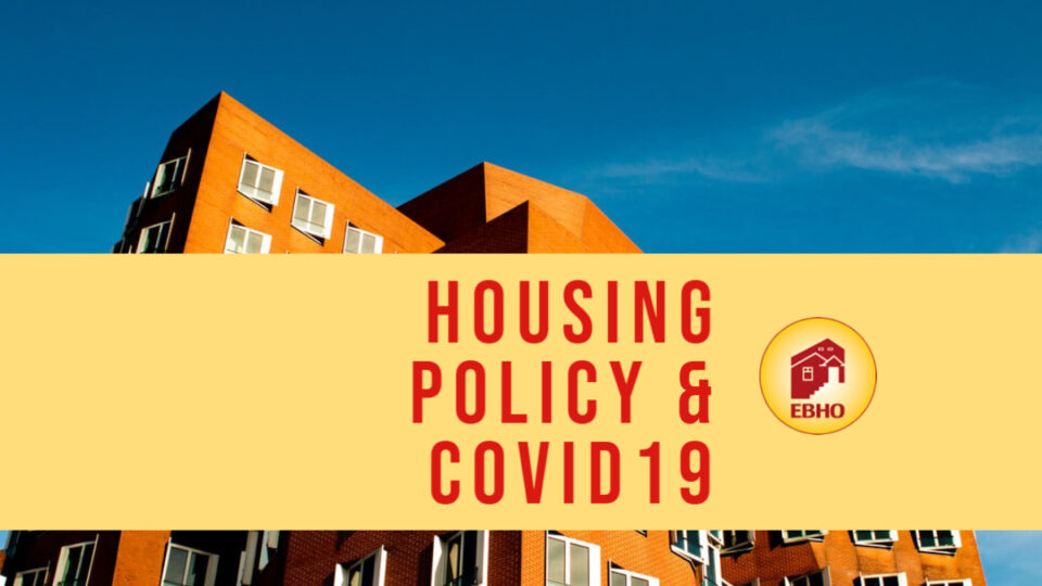 image of a blue sky and a red brick apartment building with a yellow banner through the center of the picture that reads Housing Policy & Covid19