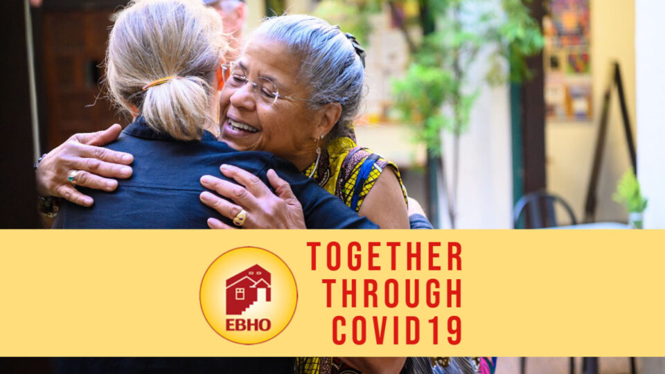 "Image of two women hugging underneath a yellow banner that reads ""Together through COVID19"""
