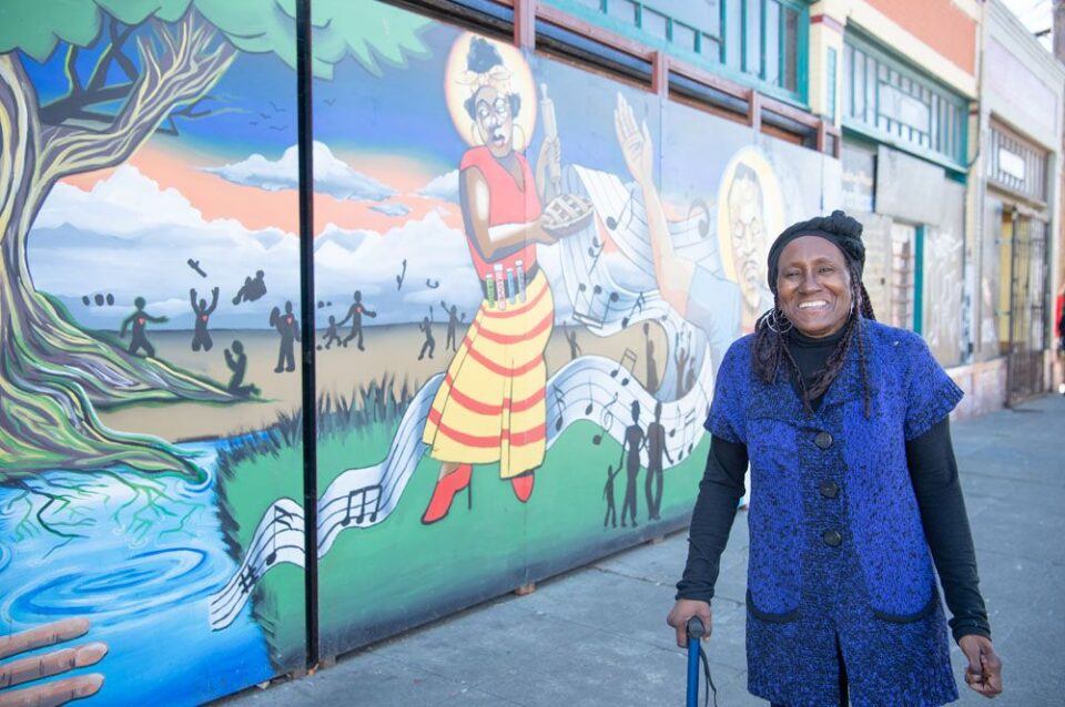 Denise, a Black elder wearing a bright blue top, smiles while looking at the camera in front of a bright mural of Ohlone people.