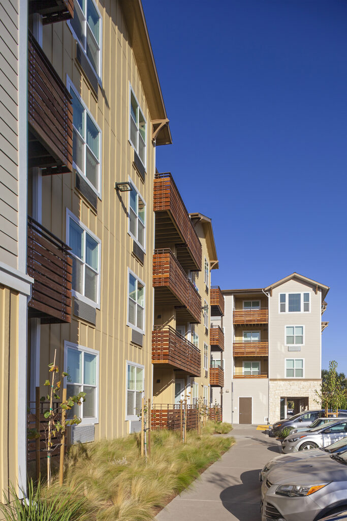 Image of a yellow and orange multi-family apartment building with a blue sky.