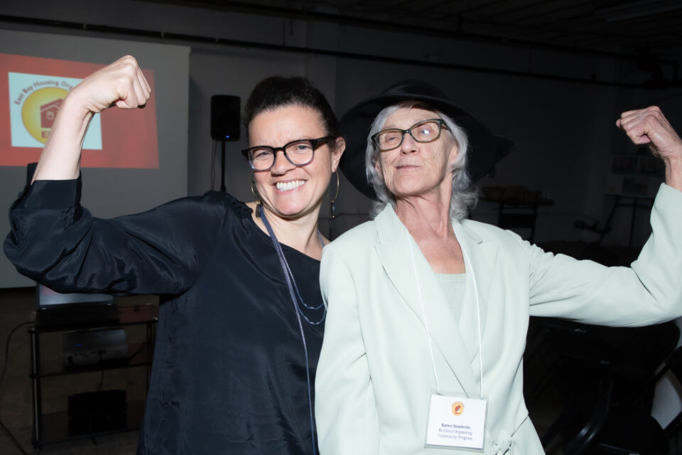 Image of two women holding their arms up in a strong muscle pose.