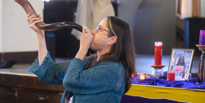 image of a woman blowing a shofar with a shrine in the background.