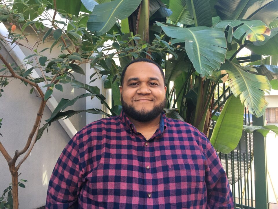 image of Damion Scott standing in front of a tree wearing a checkered shirt