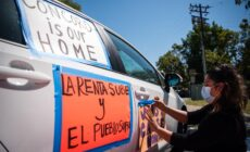 image of a woman taping an orange protest sign on the side of a car.