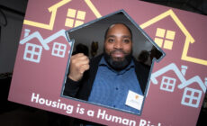 Image of a Black man with a beard holding up a Black power fist. He's looking through the cut out center of a posterboard that reads housing is a human right.